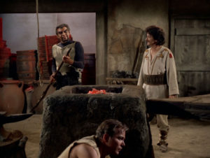 Kirk hides as the Klingon and a Villager talk