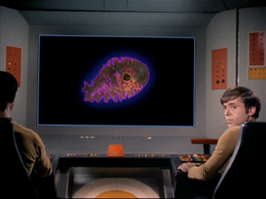 Chekov in front of the viewscreen, which displays the amoeba.