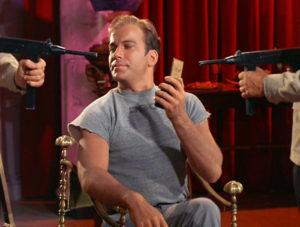 Kirk, holding a communicator and smirking.
