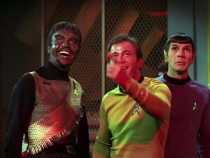 Kirk and Kang laughing at the disco ball, Spock looking puzzled.