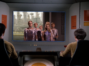 The bridge crew views the distress call from Scalos.