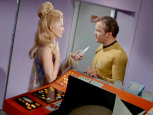 Deelah threatens Kirk with her phaser weapon.