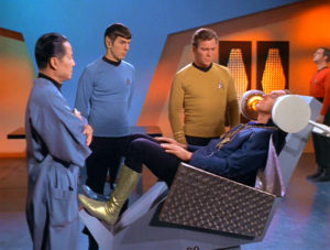 Kirk, Spock,and Governor Corey stand over Garth in the mental health chair
