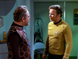 Kirk makes an agonized face at the Gideon council head
