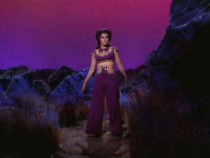 Losira's outfit, full-body. Pants, a weird belly-button cover, and All of the Purple.