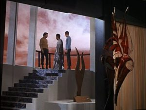 Kirk, Spock and Plasus, the leader of Stratos, stand on a balcony looking down at the planet.