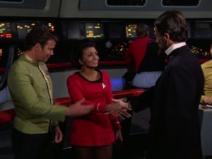 Abraham Lincoln shakes hands with Uhura, who is visibly less impressed by the mythos of Lincoln than her white crewmates.