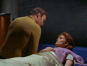 Kirk leans over Janice in a bed.