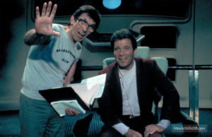 Leonard Nimoy in street clothes and glasses, standing next to Shatner in his polyester space leisure suit.