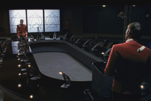 Spock and Kirk face each other from opposite ends of a conference table.